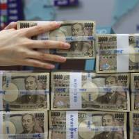 An employee stacks ¥10,000 banknotes for a photograph at the Korea Exchange Bank headquarters in Seoul on Thursday. | BLOOMBERG