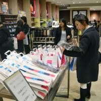 A shopper takes a look at lucky grab bags on sale for the Lunar New Year season at the Mitsukoshi department store in Ginza, Tokyo, on Jan. 31. | KYODO