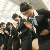 New employees practice sign language Thursday at Seven & I Holdings Co.'s annual welcoming ceremony in Tokyo. | KYODO