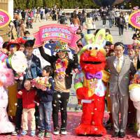 Yoshie Ishida (center) celebrates after being named visitor No. 10 million to Universal Studios Japan in Osaka on Wednesday. | KYODO