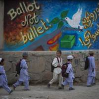 Schoolchildren pass graffiti that says 'ballot not bullet' on their way home outside Kandahar, Afghanistan, on March 12.  | AP
