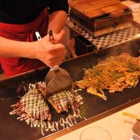 As you like it: A cook prepares the Japanese pizza/pancake-like dish known as okonomiyaki, which can be translated as 'cooked the way you like.'  © Y. | SHIMIZU/JNTO