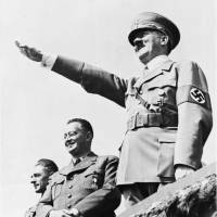 German Chancellor Adolf Hitler smiles as he salutes a huge crowd at a sports meeting in Breslau, Poland, July 31, 1938, in which Sudetic Germans participated. Behind Hitler are Konrad Henlen, pro-Nazi Czechoslovakian politician (left) and Ernst Kundt, Deputy Chief of the Sudetic German Party. | AP