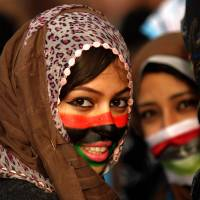 A Libyan anti-government protester with her face painted in the colors of Libya's former national flag takes part in a gathering in the city of Benghazi in February 2011. | AFP-JIJI