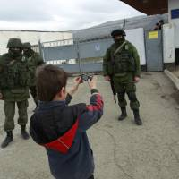 A boy photographs military personnel, believed to be Russian servicemen, standing outside a Ukrainian military unit's base outside Simferopol on Tuesday.    REUTERS
