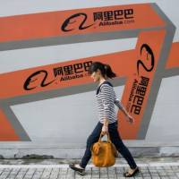 A Chinese woman walks past an Alibaba advertisement on a wall in Hangzhou, Zhejiang province, in this file picture.   REUTERS