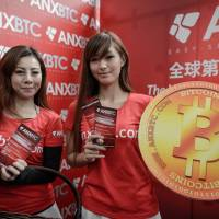 Models pose during the opening ceremony of Hong Kong's first bitcoin retail shop Friday. Bitcoin was invented in 2009 in the wake of the global financial crisis by a computer guru using the pseudonym Satoshi Nakamoto. Unlike other currencies, it does not have the backing of a central bank or government. | AFP-JIJI