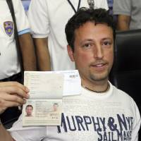 Italian Luigi Maraldi, whose stolen passport was used by a passenger boarding a missing Malaysian airliner, shows off his passport as he reports to Thai police at Phuket police station in Southern Thailand's Phuket province on Sunday. | AP