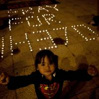 A child stands near candles being lit during a vigil for missing Malaysia Airlines passengers in Kuala Lumpur's Independence Square on Monday. | AFP-JIJI