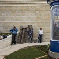 Workers stand next to a movie poster for the film 'American Hustle,' translated into Hebrew as 'American Dream,' outside a cinema in Jerusalem on Thursday. It was renamed because there is simply no word here that captures the true essence of the word 'hustle.' | AP