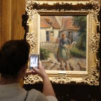 A visitor at the Fred Jones Jr. Museum of Art at the University of Oklahoma takes a photograph of 'Shepherdess Bringing in Sheep' by French impressionist artist Camille Pissarro, on Feb. 8, 2014. | AP
