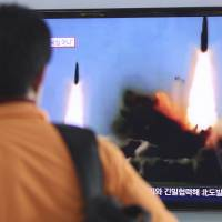 A passer-by watches a missile launch conducted Wednesday by North Korea on a TV news program at Seoul Railway Station. Pyongyang test-fired two medium-range ballistic missiles in a defiant challenge to a rare three-way summit of its archrivals, South Korea, Japan and the U.S., that focused on the North Korean security threat. | AP