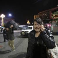 A woman reacts at the scene of a mass knife attack outside a railway station in Kunming, southwestern China, on Saturday. At least 33 people were killed and scores wounded in the violence, which the government has blamed on ethnic Uighur separatists. | AP