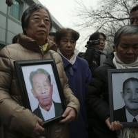 Relatives hold portraits of victims of Japan's forced labor during World War II, as they stand outside a court in Beijing on Feb. 26. | REUTERS