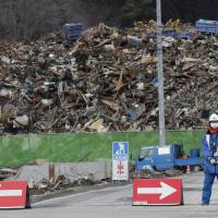 A guard keeps an eye on piles of debris generated by the March 11, 2011, earthquake and tsunami in Onagawa, Miyagi Prefecture, in March 2012. | AP