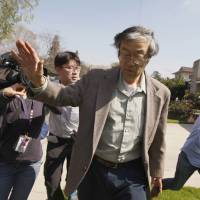 Satoshi Nakamoto is surrounded by reporters as he leaves his home in Temple City, California, on Thursday. | REUTERS