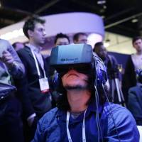 Show attendees play a video game wearing Oculus Rift virtual reality headsets at the Intel booth at the International Consumer Electronics Show in Las Vegas in January. Facebook said Tuesday that it has agreed to buy Oculus for $2 billion, betting that its virtual reality may be a new way for people to communicate, learn or be entertained. | AP