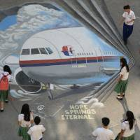 Students stand next to a giant mural featuring missing Malaysia Airlines Flight MH370 displayed on the grounds of their school in Manila's Makati financial district Tuesday. | AFP-JIJI