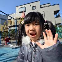A girl smiles at a playground in Tokyo in March 2013. The number of children waiting to enter nursery schools was down 2,009 from the previous year to 44,118 as of Oct. 1, 2013, the Health, Labor and Welfare Ministry said Friday. | AFP-JIJI