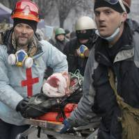 Activists evacuate a wounded protester during clashes with police Feb. 20 in Kiev's Independence Square, the epicenter of the country's current unrest. | AP