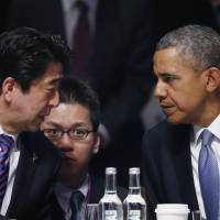 U.S. President Barack Obama talks to Prime Minister Shinzo Abe at the opening session of the Nuclear Security Summit in The Hague on Monday.   AP