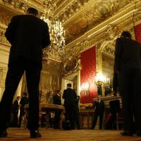 Delegation members wait outside the meeting room where dignitaries, including Russian Foreign Minister Sergey Lavrov and U.S. Secretary of State John Kerry, were discussing the Ukraine crisis at the Quai d'Orsay in Paris on Wednesday. | AP