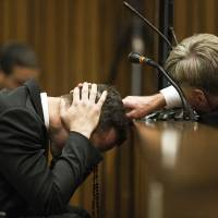 Oscar Pistorius holds his head in his hands while listening to witness testimony about the morning of the fatal shooting of his girlfriend, Reeva Steenkamp, on the fourth day of his murder trial at the high court in Pretoria on Thursday. | AP