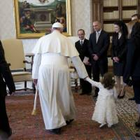 Pope Francis holds the hand of Giorgia May, the granddaughter of Malta President George Abela (left), during a private audience in the pontiff's studio at the Vatican on Friday. | AFP-JIJI