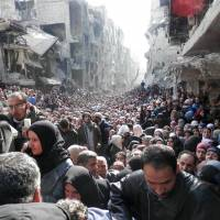 Residents of Syria's besieged Yarmouk refugee camp, south of Damascus, crowd a destroyed street during a food distribution drive on Jan. 31. U.N. investigators said Tuesday they had enough solid proof of war crimes committed by both sides in the Syrian civil war to prepare any indictment. | AFP-JIJI