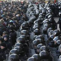 Riot police block the entrance of the regional administrative building during a pro-Russian rally in Donetsk, Ukraine, on Sunday. | AP