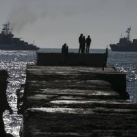 People watch Russian ships blockading the exit of Donuzlav Bay in Crimea, where three Ukrainian Navy ships have refused to surrender to Russian forces, on Sunday.   REUTERS