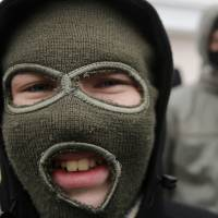 A person wearing a balaclava attends a rally against the breakup of Ukraine in the Crimean capital of Simferopol on Tuesday. | AP