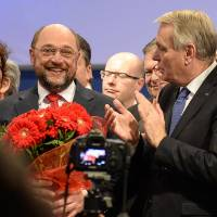 European Parliament President Martin Schulz, who was offered a bunch of flowers, is applauded by French Prime Minister Jean-Marc Ayrault (right) and other delegates at the Party of European Socialists' electoral congress on Saturday in Rome. | AFP-JIJI
