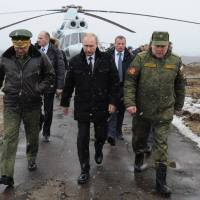Russian President Vladimir Putin (center), Defense Minister Sergei Shoigu (left) and Anatoly Sidorov, the commander of the Western Military District, walk upon arrival to watch military exercise near St. Petersburg, Russia, on Monday.   AP