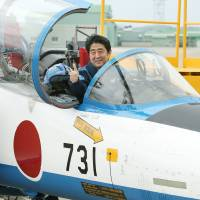 Prime Minister Shinzo Abe poses inside a T-4 training jet used by the Air Self-Defense Force's Blue Impulse aerobatic demonstration team at Matsushima Air Base in Higashimatsushima, Miyagi Prefecture, last May. | AFP-JIJI