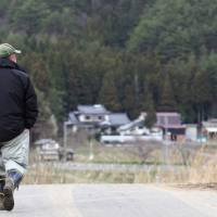 A man walks through the village of Iitate, Fukushima Prefecture, in April 2011, a little more than a month after the March 11 disaster at the Fukushima No. 1 nuclear power plant. The government decided Friday to postpone the lifting of its evacuation advisory in Iitate and the village of Katsurao by one year, until March 2015, due to delays in radiation decontamination work. | BLOOMBERG