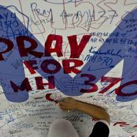 A Malaysia Airlines employee writes a message expressing prayers and well-wishes for passengers onboard missing Malaysia Airlines flight MH370 at Kuala Lumpur International Airport on Friday. | AFP-JIJI