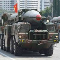 Medium-range ballistic missiles are shown off during a North Korean military parade in Pyongyang last July. The North test-fired two medium-range ballistic missiles Tuesday, a defiant challenge to a meeting by the leaders of rivals South Korea, Japan and the United States that focused on the Pyongyang's security threat. | KYODO