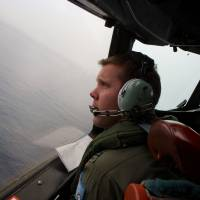 A Royal Australian Air Force AP-3C Orion pilot looks out of the window of his aircraft while searching for missing Malaysia Airlines Flight MH370 over the southern Indian Ocean on Monday. | AFP-JIJI