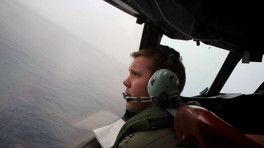 A Royal Australian Air Force AP-3C Orion pilot looks out of the window of his aircraft while searching for missing Malaysia Airlines Flight MH370 over the southern Indian Ocean on Monday.