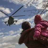 A Ukrainian MI-8 military helicopter is seen near the village of Salkovo in the Kherson region adjacent to Crimea on Tuesday. | REUTERS