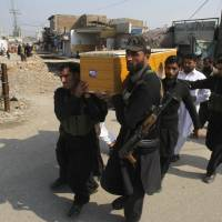 In a funeral procession, Pakistani security personnel carry the body of a fellow officer who was killed in a bomb blast Saturday. | AP