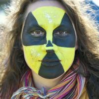 A protester with a radioactive sign painted on her face takes part in a demonstration on the first day of the two-day nuclear security summit at The Hague on Monday.   AP