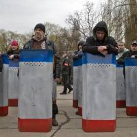 Volunteers of a self-defense group lean on their shields while waiting to attend the swearing-in of the first unit of a pro-Russian armed force, dubbed the 'military forces of the autonomous republic of Crimea' in Simferopol, Ukraine, on Saturday. | AP