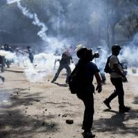 Anti-government demonstrators take cover from tear gas fired by the Bolivarian National Police during clashes in Caracas on Wednesday. | AP