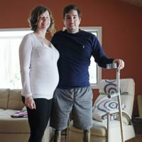 Jeff Bauman, who lost both legs in the Boston Marathon bombings, then helped authorities identify the suspects, poses with his expectant fiancee, Erin Hurley, their home in Carlisle, Massachusetts, on March 14. | AP