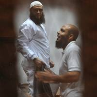 Islamist defendants accused of terrorism-related charges look through their cage bars in a Nasr City cell trial with other defendants at a courtroom in Cairo on Wednesday. The trial was adjourned to Monday. | AP