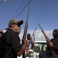 Masked, armed vigilantes sit in the back of a pickup truck at the entrance to the town of Ayutla, Mexico, in January 2013. | AP