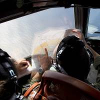 Flight Lt. Jayson Nichols looks at a map as he flies aboard a Royal Australian Air Force AP-3C Orion aircraft searching for the missing Malaysia Airlines Flight MH370 over the southern Indian Ocean on Thursday. | AFP-JIJI