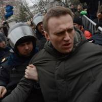 Police officers detain protest leader Alexei Navalny outside a Moscow court Monday, during a protest against the trial of eight people accused of instigating mass riots after an opposition rally on Moscow's on Bolotnaya Square turned violent on the eve of Vladimir Putin's inauguration as president in 2012. | AFP-JIJI